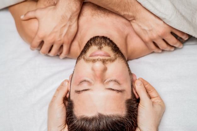 Bel giovane che riceve rilassante massaggio alla testa a quattro mani di due massaggiatori nel centro termale