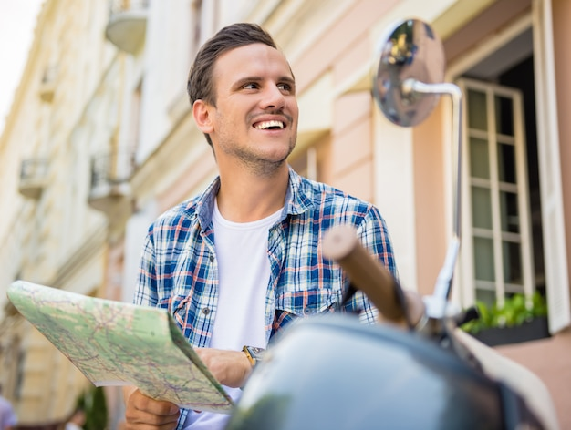 Bel giovane è seduto su uno scooter con una mappa.