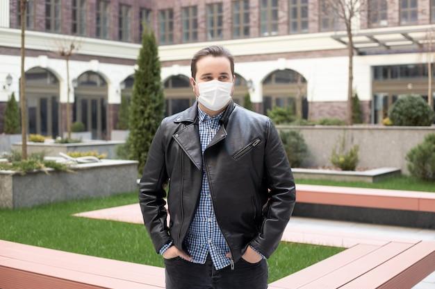 Bel giovane europeo in abiti eleganti per la strada con una maschera medica, coronavirus, malattia, infezione, quarantena, maschera medica