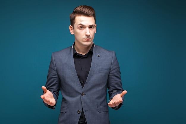 Bel giovane imprenditore in giacca grigia, orologio costoso e camicia nera