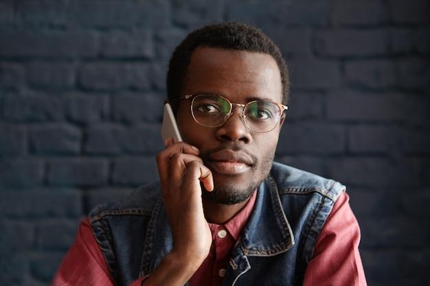 Bel giovane maschio africano con gli occhiali alla moda parlando al cellulare con la sua ragazza, in attesa di lei