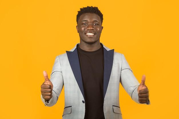 Bel giovane maschio africano in giacca con gesto della mano