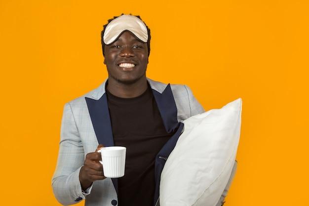 Bel giovane maschio africano in giacca sportiva con cuscino e tazza