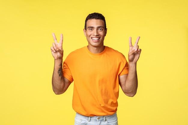 Bel giovane maschio allegro in maglietta arancione, sorridente ottimista, fare segno di pace o virgolette, in piedi sfondo giallo, esprimere positività e ottimismo, in piedi sfondo giallo
