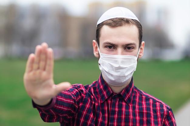 Bel giovane ragazzo ebreo nel tradizionale copricapo maschile ebraico, cappello, boma o yiddish sulla testa. uomo in maschera medica sul viso che mostra il palmo, segnale di stop contro il coronavirus, pandemia virale. covid-19