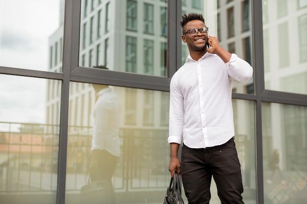 Bel giovane uomo africano in una camicia bianca con un telefono in mano vicino a un edificio di vetro