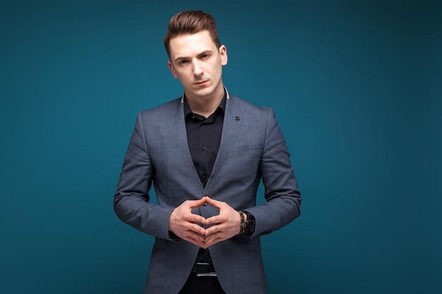 Bel giovane uomo d'affari in giacca grigia, costoso orologio e camicia nera