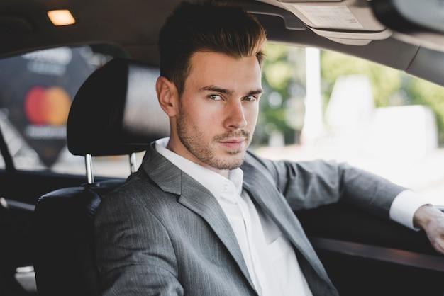 Bel giovane uomo d'affari in macchina