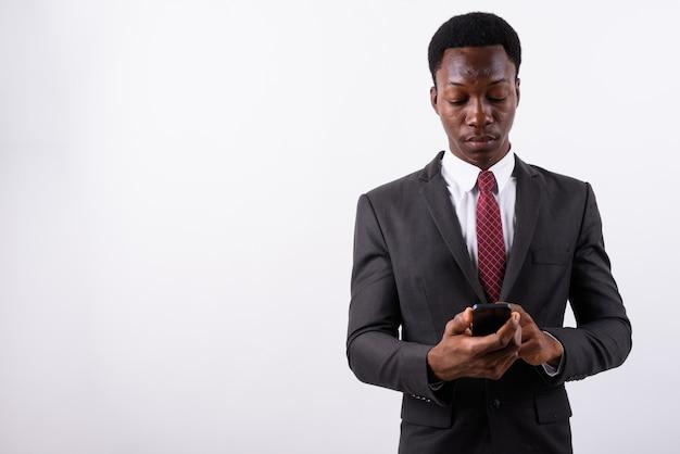 Bel giovane uomo d'affari utilizzando il telefono cellulare contro il bianco
