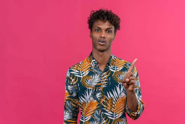 Bel giovane uomo dalla pelle scura indica con il dito indice che finalmente ha ottenuto idee eccellenti condividendo il suo piano e sciocco