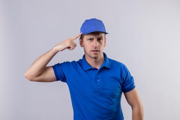 Bel giovane uomo di consegna in uniforme blu e cappuccio che punta la tempia con il dito