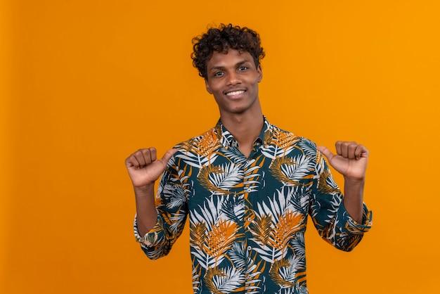Bel giovane uomo in foglie stampate camicia puntare il pollice contro se stesso