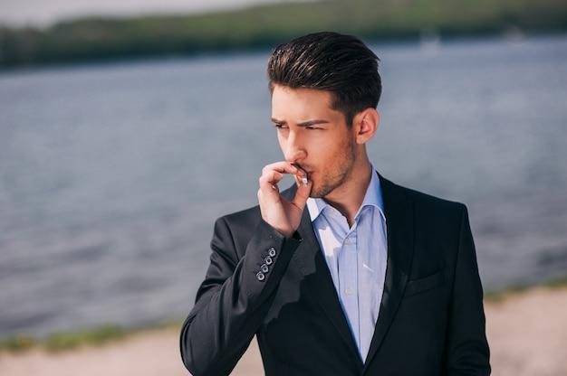 Bel giovanotto fuma sul lago