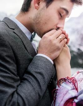 Bel marito sta baciando teneramente le mani della moglie con gli occhi chiusi, felice matrimonio
