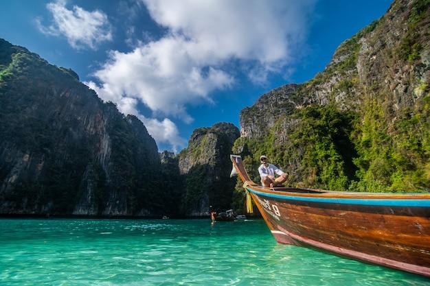 Bel maschio che gira su una barca di legno retrò sul mare delle andamane e dietro di lui puoi vedere ko phi phi lee island.