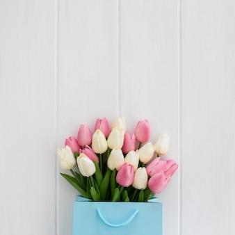 Bel mazzo di tulipani all'interno di una borsa blu su un fondo di legno bianco