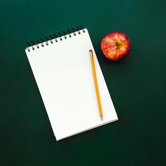 Bel notebook con mela e matita sulla lavagna di scuola