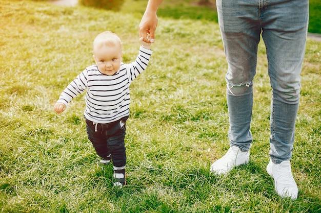 Bel padre alto ed elegante in un maglione e jeans sta martellando con il suo piccolo dolce figlio