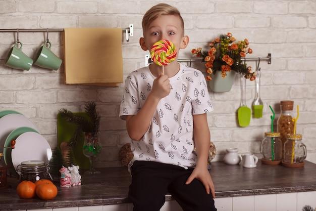 Bel ragazzino biondo è seduto sul tavolo della cucina con una grande lecca-lecca in mano. caramelle squisite