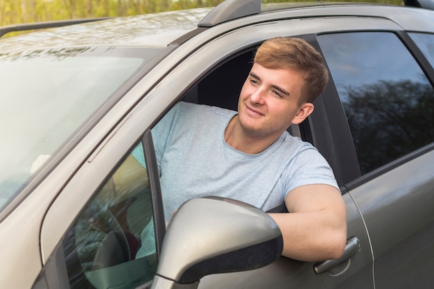 Bel ragazzo allegro, autista, giovane uomo positivo, alla guida della sua auto, sorridente, sporgono dal finestrino dell'automobile. compratore felice di una nuova auto godendo la guida. emozione, felicità, concetto di gioia