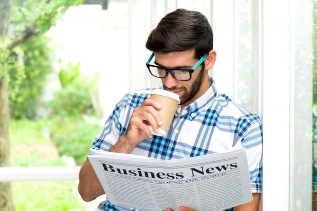 Bel ragazzo barbuto con gli occhiali sta sorseggiando caffè e leggendo il giornale, in piedi contro il pilastro sul balcone. uomo d'affari con la faccia del serio.