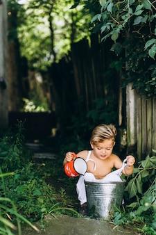 Bel ragazzo con i capelli bianchi e una combinazione si gioca con un secchio d'acqua e una tazza vicino al recinto