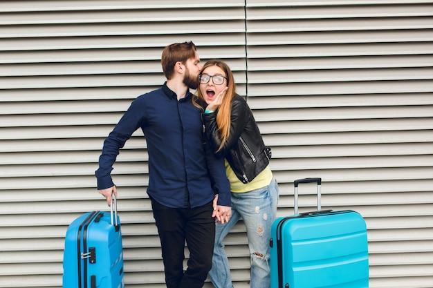 Bel ragazzo con la barba in camicia nera sta baciando la ragazza con i capelli lunghi su sfondo grigio a strisce. indossa occhiali, maglione giallo, giacca, jeans. sembra sorpreso. la coppia ha due valigie vicino.