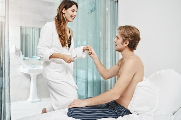 Bel ragazzo con petto nudo seduto sul letto e invitante fidanzata per unirsi a lui. gli amanti felici si sono appena svegliati e si preparano ad andare in spiaggia mentre sono in vacanza in egitto.