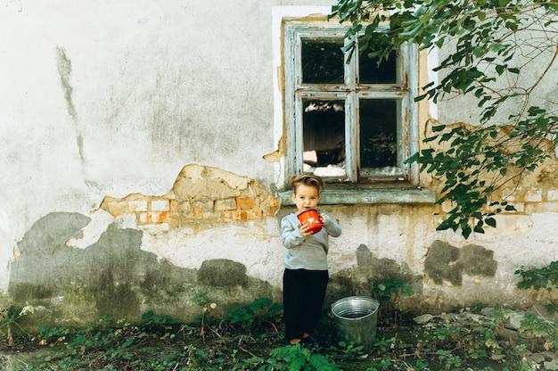 Bel ragazzo con una tazza rossa di capelli bianchi e un secchio accanto alla vecchia capanna