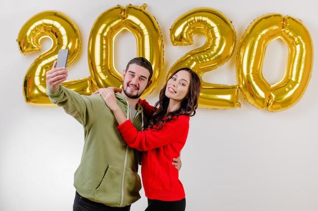 Bel ragazzo coppia e fidanzata facendo selfie di fronte al 2020 palloncini di capodanno
