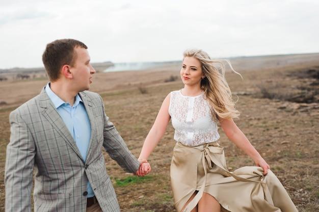 Bel ragazzo e ragazza bionda che cammina sul campo, un uomo conduce una donna che tiene la mano.