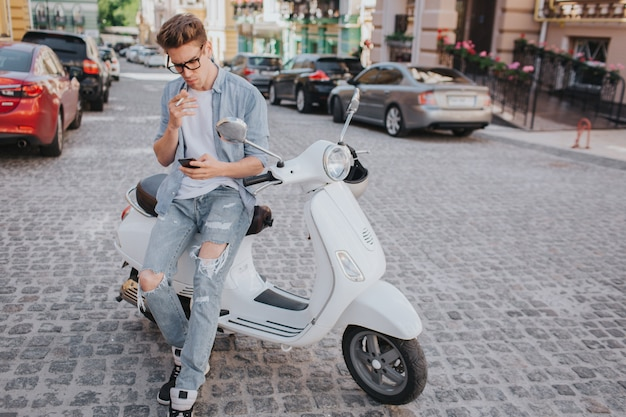 Bel ragazzo è seduto sulla moto e tenendo in mano il telefono