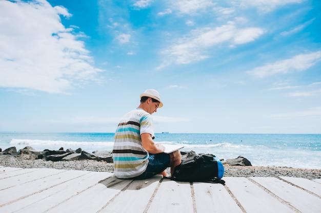 Bel ragazzo giovane fotografo che lavora con un computer portatile sulla spiaggia