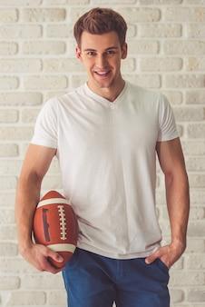 Bel ragazzo in abiti casual in possesso di un pallone da calcio