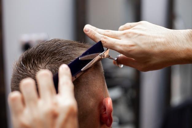Bel ragazzo ottenere un taglio di capelli dal parrucchiere, il parrucchiere kazako taglia manualmente con le forbici e un pettine, primo piano di taglio di capelli corto