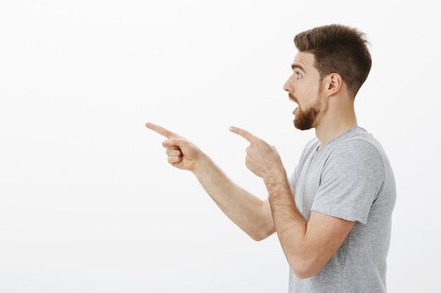 Bel ragazzo sorpreso e impressionato in piedi di profilo con la mascella abbassata e lo sguardo incuriosito che indica e guarda stupito e senza parole sul muro bianco