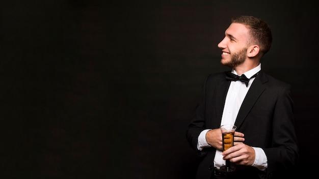 Bel ragazzo sorridente in giacca da pranzo con un bicchiere di bevanda
