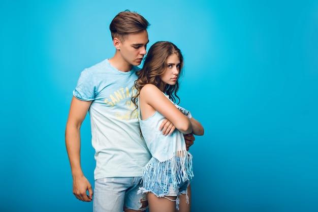 Bel ragazzo sta abbracciando bella ragazza con i capelli lunghi su sfondo blu in studio. indossa maglietta bianca, pantaloncini e sembra offesa.