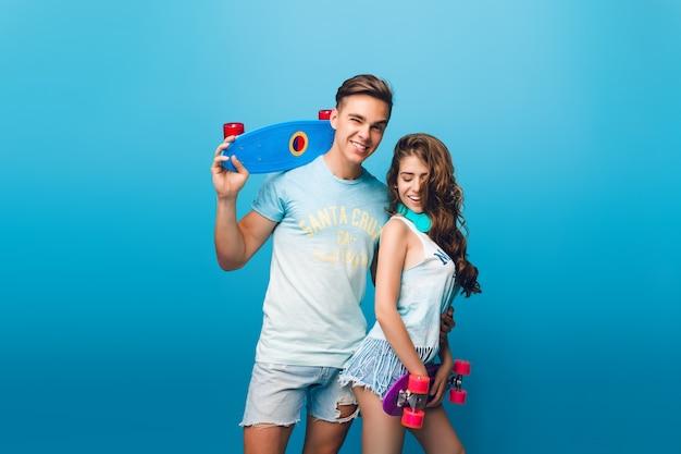 Bel ragazzo sta abbracciando bella ragazza con i capelli lunghi su sfondo blu in studio. tengono gli skateboard e si divertono insieme.