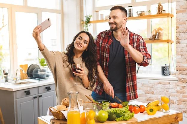 Bel ragazzo sta sorridendo e cucinando in cucina mentre la sua ragazza sta facendo selfie utilizzando uno smart phone.