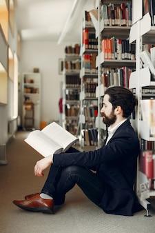 Bel ragazzo studia presso la biblioteca
