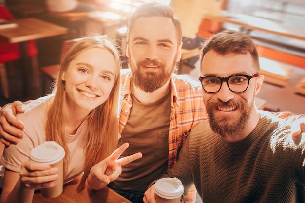 Bel selfie di due uomini e una donna seduti insieme molto vicini e in posa sulla macchina fotografica. la ragazza mostra il simbolo della pace con le dita. taglia vista.
