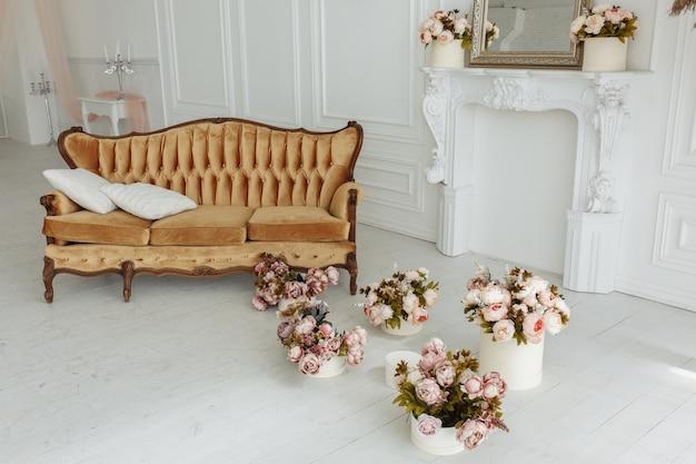Bel soggiorno provance con divano marrone vicino al camino con fiori e candele