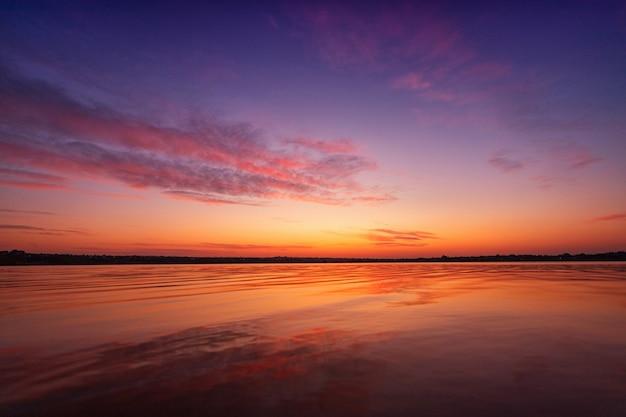 Bel tramonto sul lago con nuvole e riflessi sull'acqua