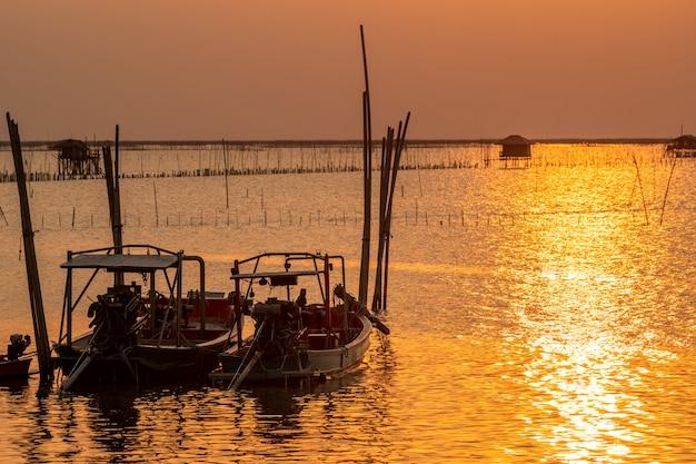 Bel tramonto sul mare. cielo e nuvole scuri e dorati di tramonto. sfondo della natura per il concetto tranquillo e pacifico. tramonto a chonburi, tailandia. maschera di arte del cielo al crepuscolo. allevamento in mare.
