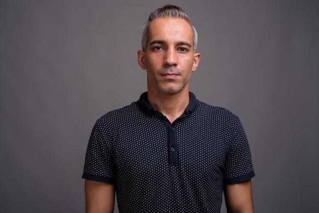 Bel uomo persiano con i capelli grigi su sfondo grigio