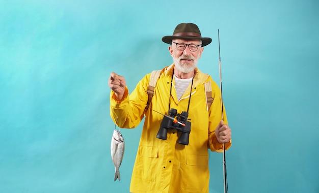 Bel vecchio pescatore fortunato, con in mano una canna da pesca con un pescato, pesce pescato, primo piano di un pescatore su un muro isolato
