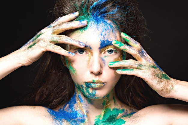 Bel viso con vernice colorata su un nero, bella ragazza, trucco colorato, donna alla moda,