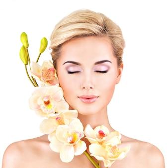 Bel viso di giovane donna graziosa con pelle sana e fiori rosa sul corpo - isolato su bianco