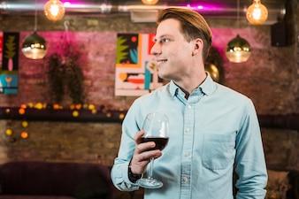 Bell'uomo sorridente nel bar con un bicchiere di vino